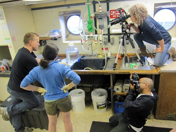 Katherine Turner, top-right, and Carlos Sanchez capture photo and video footage of work being done onboard the Thomas G. Thompson research vessel.