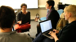 Science Trak's Norma Straw (left) consults with Comm Lead students Katya Yefimova (center), Sarah McCaffrey (right) and John Hellriegel (back to camera)