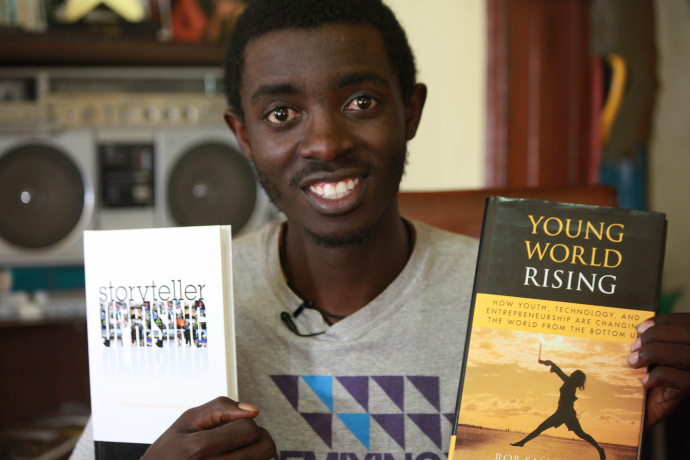 "An ""Obumu Media Lab"" student holds up two of the workshop's texts, Comm Lead's Hanson Hosein's ""Storyteller Uprising"" and Rob Salkowitz' ""Young World Rising."""