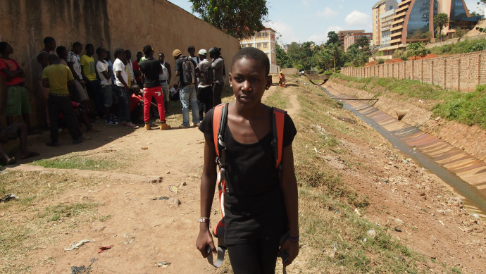 "An ""Obumu Media Lab"" student stands on the ""have nots"" side of Eye Ghetto's water canal."
