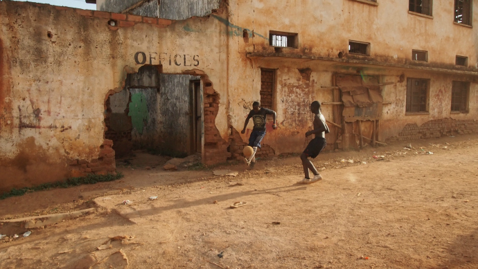 Ugandan youth play soccer in the dirt field by Kawempei's abandoned school, turned make-shift community center.